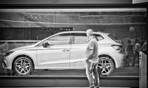 車のショーウィンドーを見つめる男性