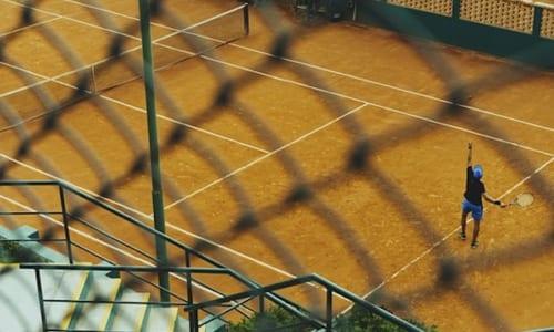 金網越しにテニスのサーブを見つめる
