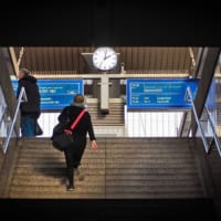 鉄道のホームに向かって階段をのぼる人