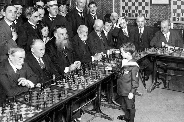 大勢の大人とチェスをする子供