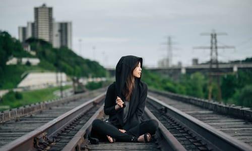 線路のうえに座る女性